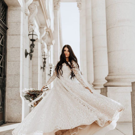 Woman twirls in modest wedding dress with beautiful lace details and long sleeves